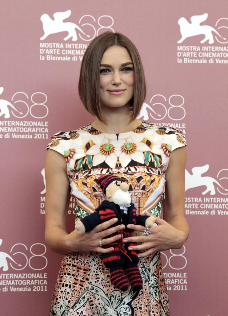 """Actress Knightley holds toy given to her by co-star Mortensen at a photocall for their film """"A Dangerous Method"""" which is in com"""