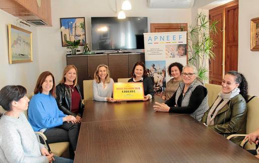 imagen de la reunión, con el cheque de 4.088,89 euros que el Ayuntamiento recaudó las pasadas Navidades.
