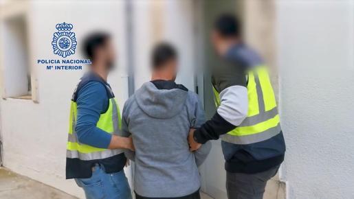 Agentes de la Policía Nacional custodian a uno de los tres detenidos en la 'trama de la cerveza'.