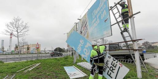 Los operarios de una empresa de publicidad desmontando los paneles el pasado 16 de febrero.