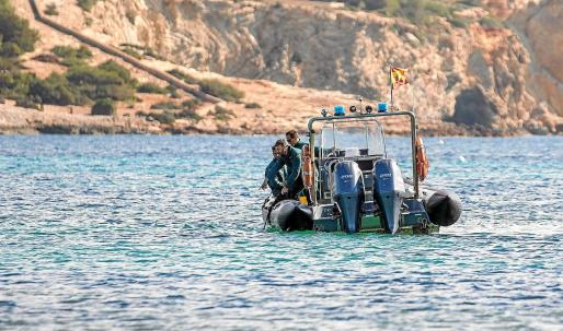 Agentes del GEAS observan el fondo de la bahía desde la embarcación para localizar los muertos en la jornada de ayer.