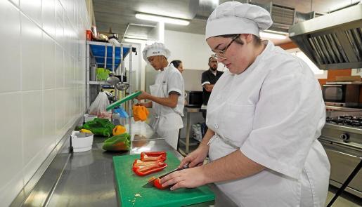 Estudiantes de la FP Básica del IES Balàfia asisten a una de las clases prácticas de cocina en las instalaciones del centro.