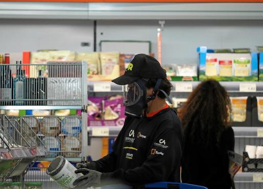 Un cliente con mascarilla y guantes realiza la compra en un supermercado de Ibiza.