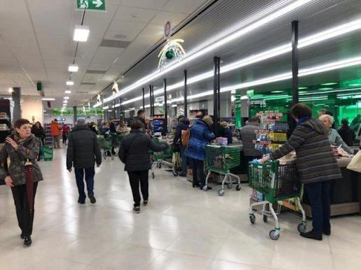 Decenas de personas hacen cola ante las cajas de un supermercado.