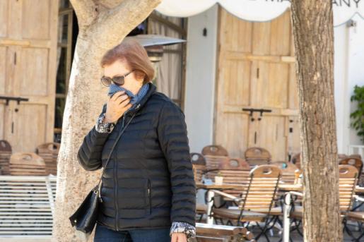 Una mujer camina con una mascarilla por una calle de Ibiza.
