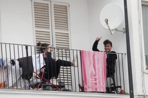 Dos vecinos de Ibiza intentan superar el aislamiento social impuesto por el coronavirus saliendo a su balcón.