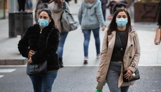 Varias personas pasean con mascarilla por Barcelona