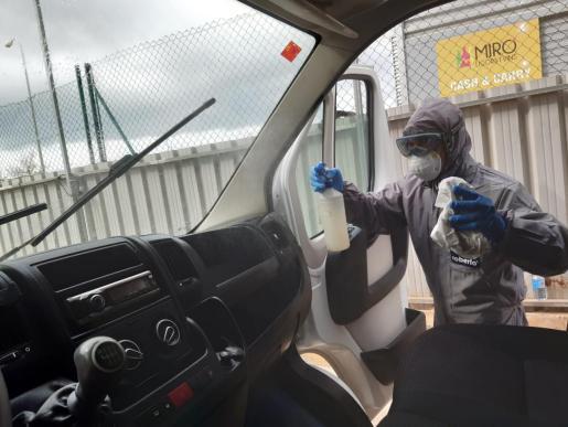 Un empleado de estos talleres procede a la desinfección de uno de estos vehículos.