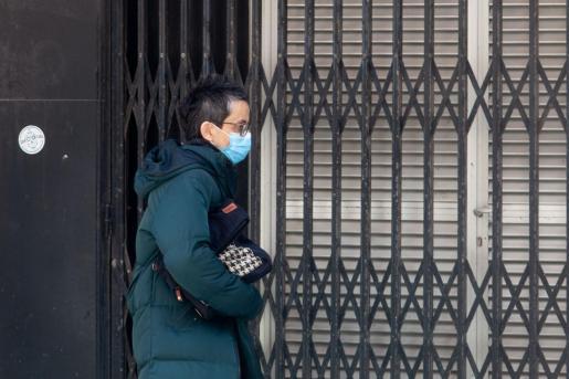 Una señora con mascarilla pasa frente a un comercio cerrada.