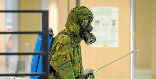 Uno de los efectivos de la unidad armado con una mochila de fumigación para combatir la existencia de elementos contaminados en el aeropuerto de Ibiza.