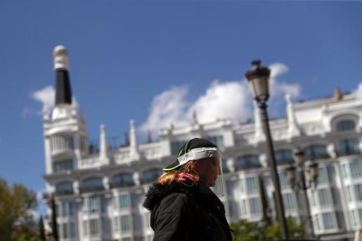 Una mujer, con una máscara protectora, caminando por Madrid.