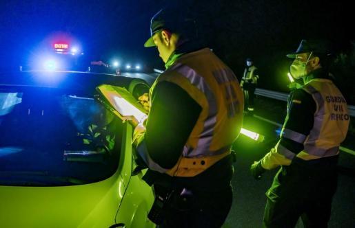 Un conductor muestra su documentación a los agentes en un control de movilidad interurbana de la Guardia Civil de Tráfico.