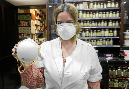Una farmacéutica de la farmacia Tur Viñas muestra una mascarilla.