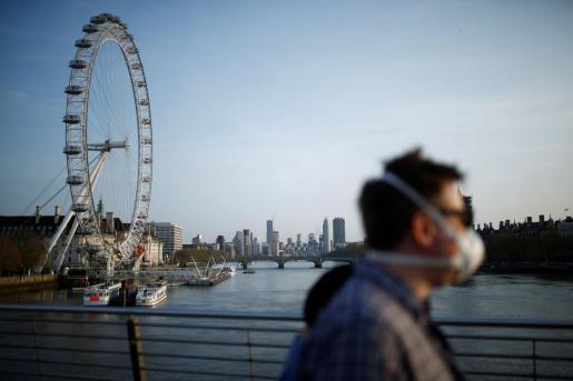 Un hombre con mascarilla cruza el punte Golden Jubilee en Londres.