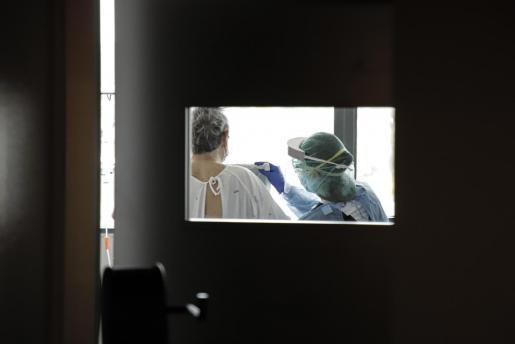 Una sanitaria, atendiendo a un paciente.