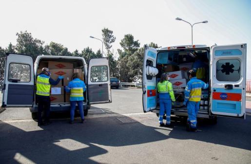 Voluntarios entregan mascarillas en Catania.