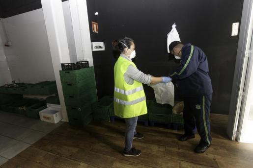 Un usuario recoge su comida de manos de una de las voluntarias
