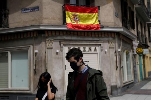 Un hombre con mascarilla pasa pro delante de un balcón con la bandera de España.