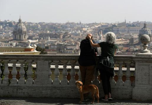 Un pareja con un perro mira el paisaje en Roma.