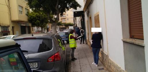 Imagen de la cola de gente que esperaba ayer para recibir alimentos mientras una voluntaria toma datos.