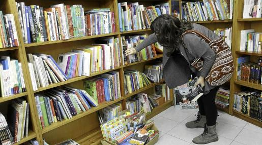 Una mujer busca diferentes títulos entre las estanterías de la Librería Hipérbole en un Sant Jordi inusual por la pandemia de la COVID-19.