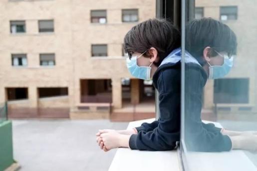 Un niño con una mascarilla se asoma a la ventana de su casa cuando queda tan solo una semana para que niños y preadolescentes puedan salir a la calle durante el confinamiento por el coronavirus, en Valdemoro/Madrid (España) a 20 de abril de 2020 - OSCAR J. BARROSO - EUROPA PRESS