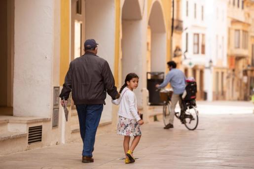 Una niña pasea de la mano de un adulto.