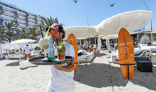 imagen de archivo de un camarero llevando las consumiciones en un beach club.