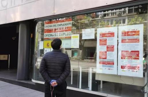 Un hombre pasa con su perro frente a una oficina de Empleo en la capital - Marta Fernández Jara - Europa Press