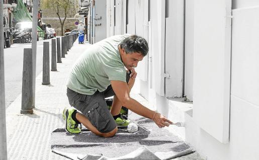 Un comerciante pinta la fachada de su local ante la posible reapertura del próximo lunes.