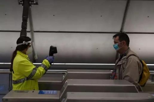 Una voluntaria de la DYA toma la temperatura con una pistola a un viajero en la estación de metro de Otxarkoaga. En Bilbao (Vizcaya, País Vasco, España), a 11 de mayo de 2020. - H.Bilbao - Europa Press