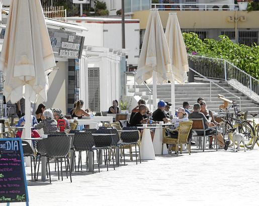 Varias personas toman algo en una terraza de ses Figueretes.