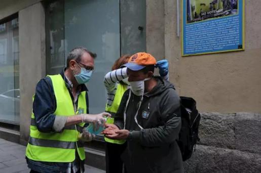 Una voluntaria de Mensajeros de la Paz ayuda a un hombre a ponerse una mascarilla. - Marta Fernández Jara - Europa Press