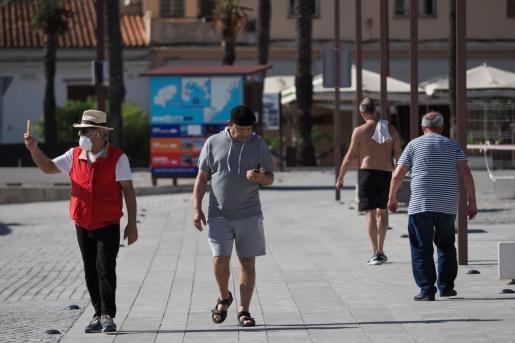 Un grupo de personas pasean por el puerto de Ibiza.