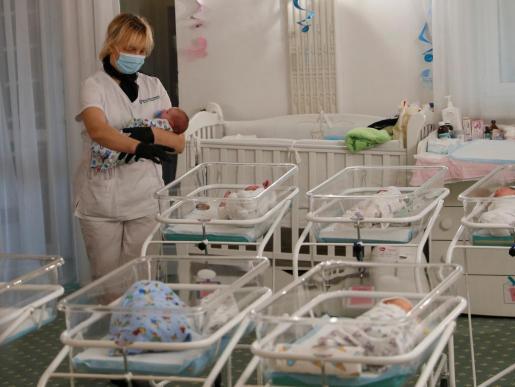 Una enfermera, junto a varios recién nacidos en un hotel de Kiev.