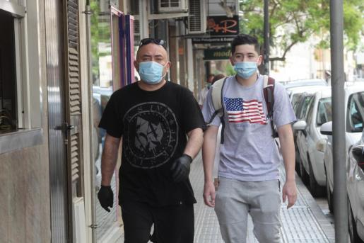 Dos personas pasean con mascarilla por Ibiza.