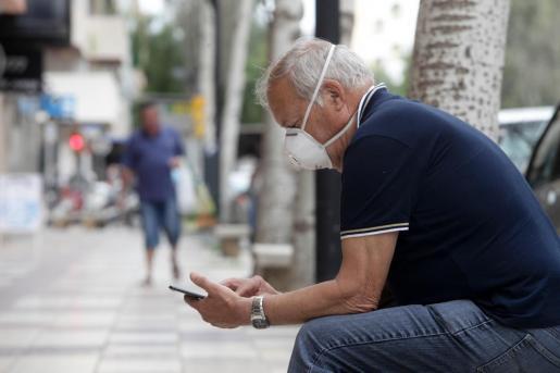 Un ciudadano consulta su móvil sentado en un banco de Vila.