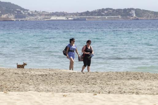 Dos personas caminan por una playa de Ibiza.
