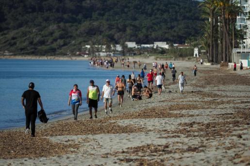 Varias personas pasen por la playa.