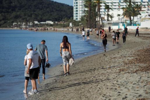 Varias personas caminan por la playa de ses Figueretes.