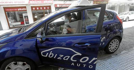 El profesor de la autoescuela, con pantalla protectora y mascarilla, adecua el coche para una clase práctica.
