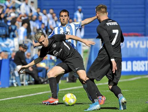 Javi Lara protege la pelota ante la presión de un jugador del Atlético Baleares en el partido celebrado esta temporada en Son Malferit.
