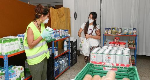 Una mujer recoge alimentos en compañía de una de las voluntarias.