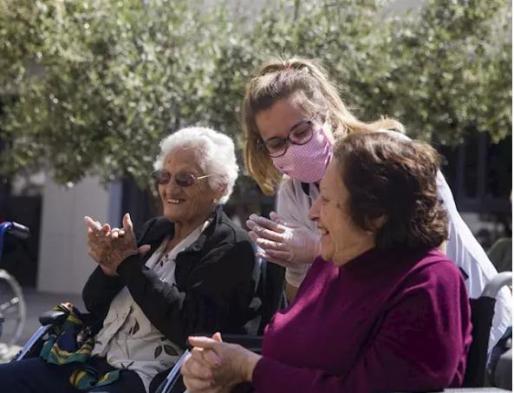 Dos residentes de la residencia de mayores Vitalia Kansas salen al patio durante unos minutos para celebrar que no hay ningún caso de contagio por coronavirus hasta la fecha. En Sevilla, (Andalucía, España), a 26 de marzo de 2020.
