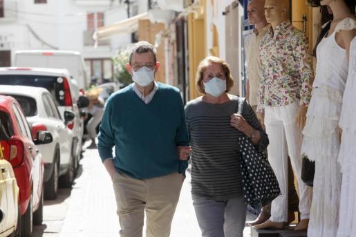 Dos personas pasen con mascarilla por Vila.