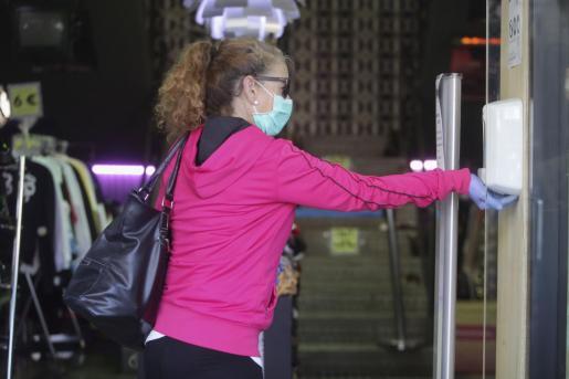 Una señora se echa gel hidroalcohólico en las manos.