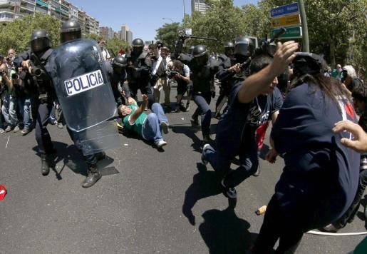 Agentes antidisturbios se enfrentan a participantes en la manifestación.