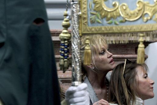 La actriz estadounidense Melanie Griffith observa la salida del trono de María Santísima de Lagrimas y Favores en las Cofradías Fusionadas.