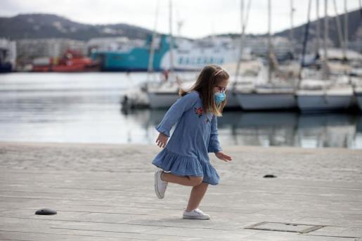 Una niña, con mascarilla en el puerto de Ibiza.