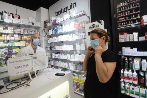 Una señora adquiere una mascarilla en una farmacia.